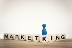 King pawn on the word Marketing Stock Images