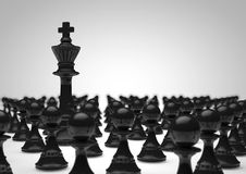 King and pawns. Black chess king surrounded by black pawns Royalty Free Stock Images
