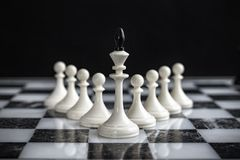 The king and pawns on a chess Board on a dark background royalty free stock photos