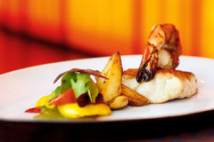King prawn served with cod and roasted wedges Royalty Free Stock Photo