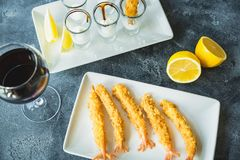 King prawn served with sauce and lemon. Sea food with glass of wine drink. King prawn served with sauce and lemon. Sea food with glass of wine Royalty Free Stock Images
