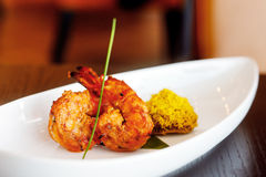 King Prawn Tikka with a saffron rice cake Stock Images