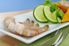 King Prawns. Raw king prawn with lime slices and lettuce on white plate, wooden board and green table mat with cutlery and blue background  (Selective Focus Royalty Free Stock Images