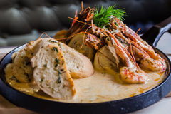 King prawns cooked in sauce with garlic toasts Royalty Free Stock Photography