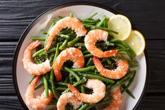 King prawns with green beans, cheese and lemon close-up on a pla Stock Photo