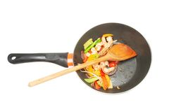 Stir fry prawns and veg. King prawns and vegetables with a wooden spoon in a wok isolated against white Royalty Free Stock Photography