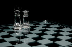 King and queen. Two glass chess  figures king and queen  on chessboard Royalty Free Stock Photo