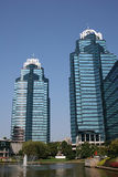 King and Queen 4. Twin blue office towers by lake against blue sky Stock Images