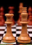 King and Queen on chess board. Light colored wooden chess king and queen in sharp focus with dark pieces out of focus across the chess board royalty free stock image