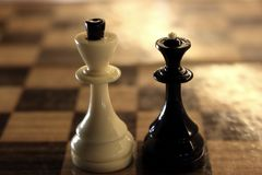 King and queen chess figures on chessboard. White king and black queen. Competition and strategy concept. royalty free stock photo