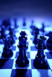 King and queen chess pieces. Closeup shot of the king and queen on a blue toned chessboard. Depicting game and kingdom. Royal subjects around them. Still life Stock Photo