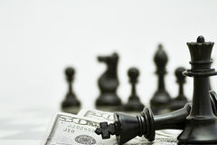 King and Queen Chess Pieces with US Currency Stock Image