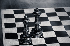 King and queen - Chess. Wooden old chessboard, black king and queen royalty free stock images
