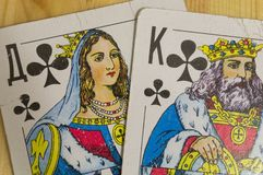 King and Queen of the cross from a deck of old playing cards. The king of spades beats the Queen of clubs from a deck of old playing cards royalty free stock photo
