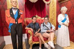 King and Queen of England wax works museum and the young girls. Two young girls getting into the moment with the king and queen elizabeth of england . Sitting on Royalty Free Stock Photo