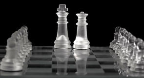 King and Queen on glass chess board Royalty Free Stock Image