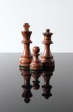 King, Queen, Pawn. Three dark wooden chess pieces on a smoked glass table and white background Stock Photography