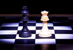 King and Queen pieces of chess game. In selective lighting stock photos