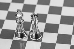 King and Queen. Rugged brass chess king and queen pieces on a chess board. Shallow DOF royalty free stock photo