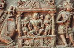 King or reach man sitting on sculpured stone relief carvings from the 12th century temple`s wall, Indian artwork Stock Image
