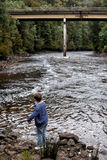 King River Tasmania. Young boy throwing rocks into the King River , with the water stained brown from Tannin, near Queenstown, west coast, Tasmania Stock Photos