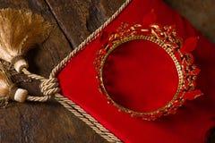King's crown on red velvet. Medieval golden king's crown on red velvet pillow Stock Image