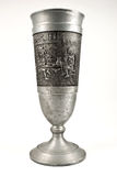 King`s Goblet. Medieval goblet with a draw representing three men sitting on a table drinking Stock Image