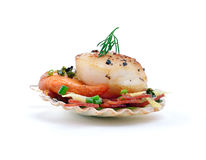 King Scallop. A single pan seared King Scallop in shell on a bed of grilled Chorizo, spinach, lemon zest and chopped chives against a white background. A perfect stock image