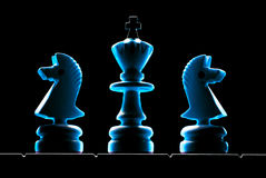 King and servants. Chessmen (king and two horses). A dark background Royalty Free Stock Images