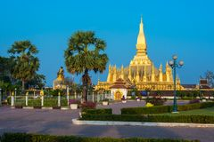 King Setthathirat statue and Pha That Luang stupa royalty free stock photo