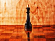 King in the shade. A small king in the shadow of a large on a chessboard, chess is a very exciting board game that is popular all over the world Stock Images