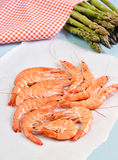 King shrimps on blue background with asparagus. On blue background royalty free stock image