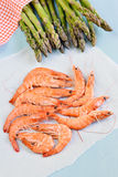 King shrimps on blue background with asparagus. On blue background stock image