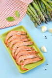 King shrimps in a green rectangular plate on blue background. With garlic and asparagus stock images