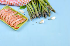 King shrimps in a green rectangular plate on blue background. With garlic and asparagus royalty free stock photography
