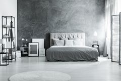Bed against dark textured wall. King-size bed against dark textured wall in monochromatic bedroom with screen and white carpet Stock Images
