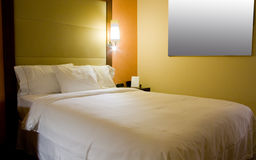 King-size bed with bedside table and lamp Royalty Free Stock Photos