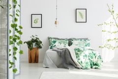 King-size bed with floral bedding. Plant on wooden designer table next to king-size bed with floral bedding in green bedroom with handmade lamp Royalty Free Stock Photography