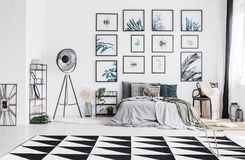 King-size bed with many pillows and grey sheets standing in whit. E bedroom interior with big studio lamp, black and white carpet and plastic chair with knit stock photos