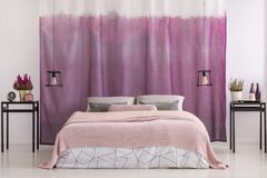 Gradient pink curtains in bedroom. King-size bed with pink blanket between lamps and nightstands with plants against gradient pink curtains in bedroom Royalty Free Stock Photography