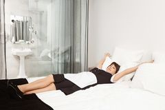 King size bed for queen. Relaxed and carefree housemaid lying and stretching on bed, feeling relieved. Maid decides to. Take nap after cleaning dirt in Stock Image