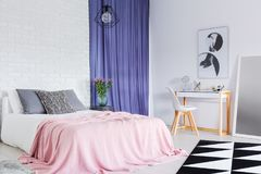 King-size bed in sophisticated bedroom. Pink coverlet on king-size bed with pillows in sophisticated bedroom with blue curtain and dressing table Stock Image