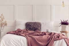 King size bed with white bedding and dirty pink blanket, real photo with copy space royalty free stock image