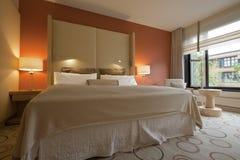 King-size Bett mit Nachttisch und Lampen Stockfotografie