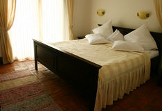 King size wooden bed. King size bed with many pillows royalty free stock photography