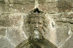 King Of The Wall. An old stone detail from a gate in Cong, Ireland shows what appears to be a king with a crown. This old sculptural element is heavily weathered royalty free stock photo