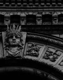 King of the zodiac standing still. Shot in black and white, detail on the sculpture on the facade of this historic building representing some characters. Set in royalty free stock photography