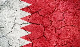 Kingdom of Bahrain flag. On dry earth ground texture background Royalty Free Stock Images
