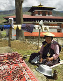 Kingdom of Bhutan - Drying Meat. An elderly Bhutanese woman drying strips of yak meat in the sun near Paro Rinphung Dzong (Buddhist Monastery) in the Kingdom of Royalty Free Stock Image