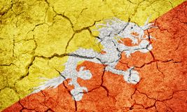 Kingdom of Bhutan flag. On dry earth ground texture background royalty free stock photography